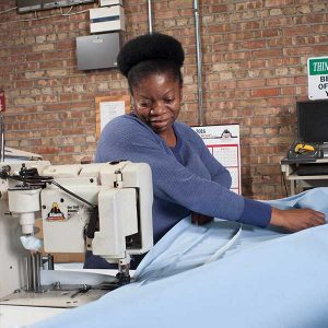 Estee Bedding worker sewing mattress cover